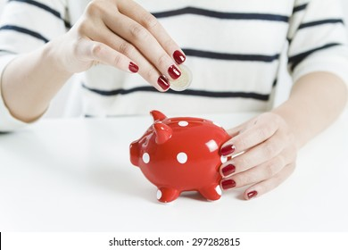 Woman saving money with red piggy bank