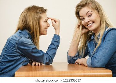 Woman saying bad things about her over confident female friend. Pointing at forehead, stupidity gesture.
