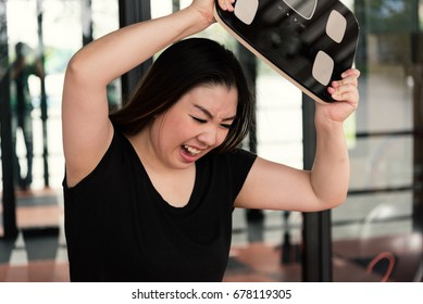 Woman with scale unhappy with her weight gesturing sadness and worry.