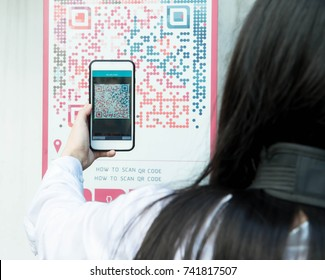 Woman scan QR code with smart phone.