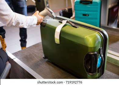 Woman Scanning Tag On Luggage At Airport Check-in