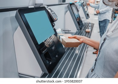 Woman scans barcode of her lunch box for cashless payment at the self-service checkout in the supermarket. Such machines kiosks allows to increase throughput and reduce queue in the store