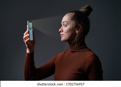 Woman scans face using facial recognition system on mobile phone for biometric identification. Future high tech technology and face id