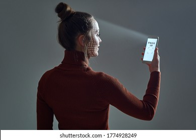 Woman scans face using facial recognition system on smartphone for biometric identification. Future high tech technology and face id