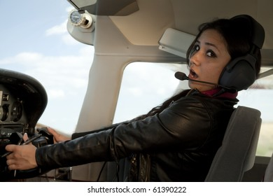 A woman is scare and flying a plane.
