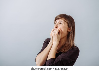 Woman scared, covered her mouth with his hands. On a gray background.