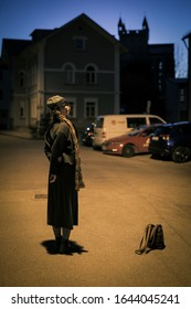 A woman in a scarf and hat stands alone on the street at night.