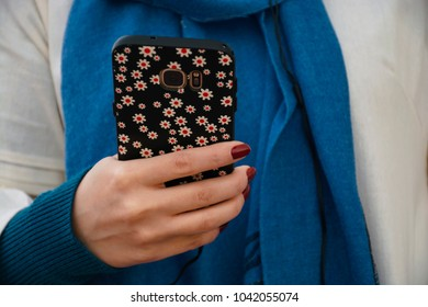 woman with scarf holding a smart phone