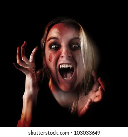 A woman is a scary vampire with pointy teeth and blood all over her hands and face. Use it for a fear or Halloween concept.