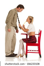 Woman in a school girl uniform pulls her teacher close by his tie. She is the one in control.