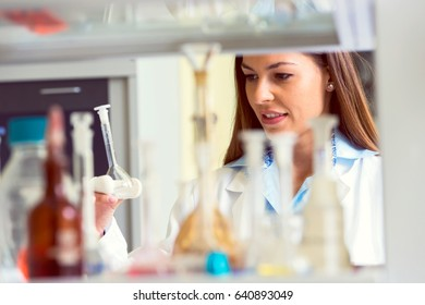 Woman scientist behind lab glassware. Scientist carrying out experiment in research laboratory