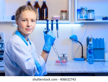 Woman scientist biochemist at the workplace makes the analysis in the modern laboratory. She is holding a dropper and a test tube