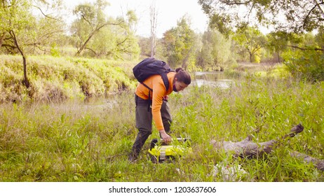 Woman scientist ecologist putting the tool box on the ground