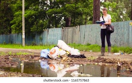Woman scientist environmentalist standing near garbage dump and making notes in the diary