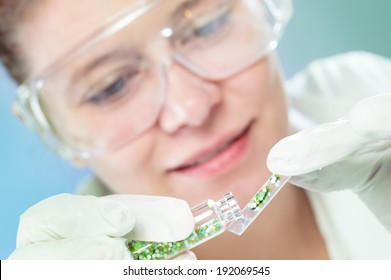 woman scientist in laboratory with glass tubes