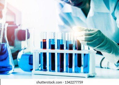 Woman scientist working in laboratory and examining biochemistry sample in test tube. Science technology research and development study concept.