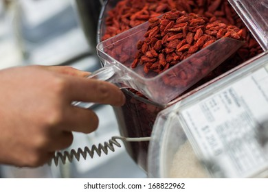 woman scooping Goji berries from the bulk food dispenser at an organic grocery store