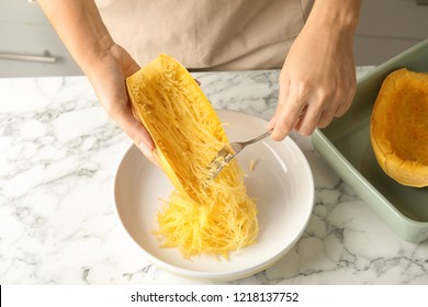 Woman scraping flesh of cooked spaghetti squash with fork in kitchen