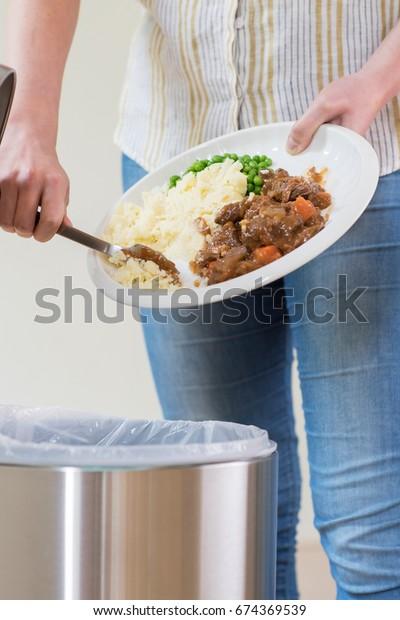 Mujer tirando sobras de comida al basurero