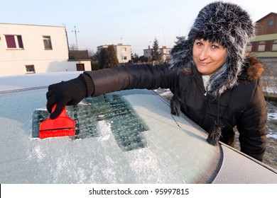 Woman scraping ice from the car window