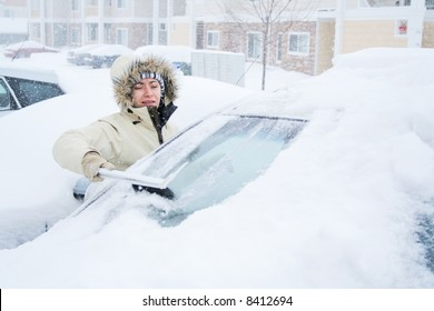 Woman scraping snow off of windshield