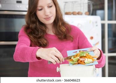 Woman Scraping Vegetable Peelings Into Recycling Bin