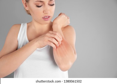 Woman scratching forearm on grey background, space for text. Allergy symptoms