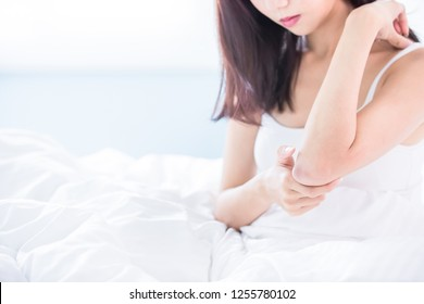 woman scratching her arm and elbow because of dry skin at home