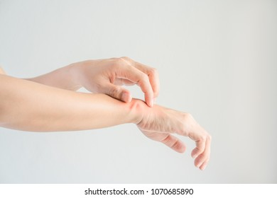 Woman scratching her wrist.