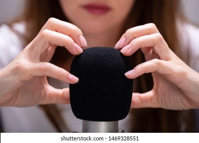Woman scratching microphone with nails to make ASMR sounds