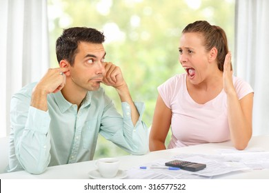 Woman screaming at her husband in argument over home economy, man not listening.
