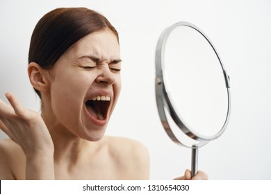 A woman screams in her hand a mirror.