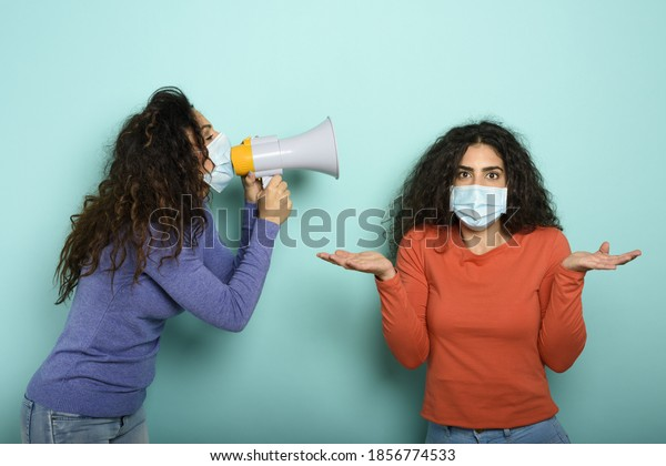 Woman screams with loudspeaker to a friend but it is difficult to understand with face mask. Cyan background