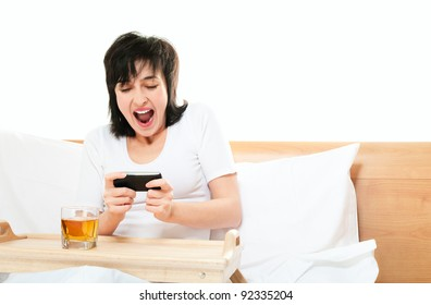 Woman screams as she plays video games on mobile phone in bed isolated on white