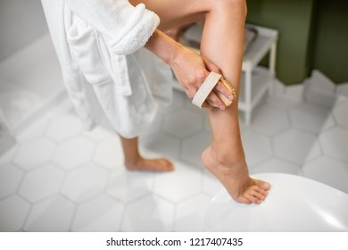 Woman scrubbing her legs with a brush making skin peeling in the bathroom