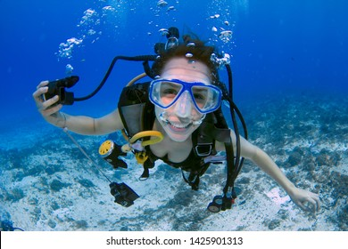 Woman scuba diver smiling underwater - scuba diver, using a blue mask, holding the regulator on one hand and smiling to the camera on a deep blue ocean, in Mexico (Cozumel island).