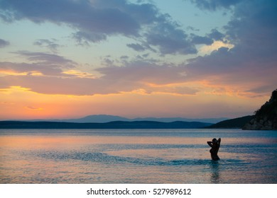 Woman in the sea at sunset