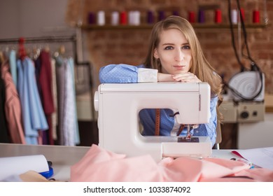 A woman seamstress, a designer in a sewing studio, the workshop has, put head on a sewing machine. Young businessman, fashion designer. Its production of clothing.
