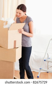 A woman is searching in a cardboard
