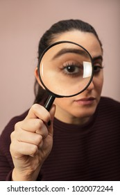 Woman searching for clues or conducting an investigation or search peering through a handheld magnifying glass , what makes his eye seem bigger