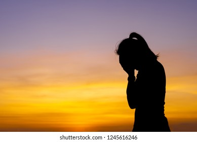 Woman seated with a life time of stress in the sunset.