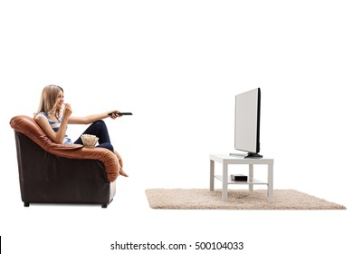 Woman seated on an armchair eating popcorn and changing TV channels isolated on white background