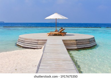 Woman seated on a beach chair enjoying vacations in an exclusive beach in the Maldives. Tourist isolated relaxing in a beautiful wooden deck.