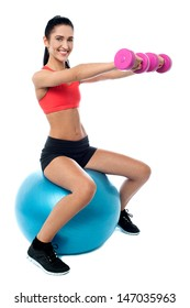 Woman seated on fitness ball doing dumbbells