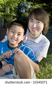 A woman is seated in a park.  She is holding her son.  They are smiling at the camera.  Vertically framed shot.