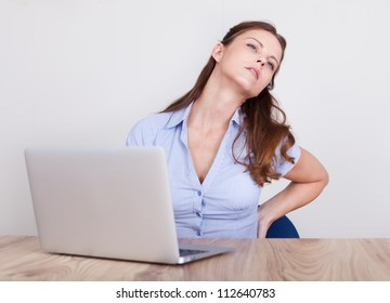 Woman seated at a table behind a laptop stretching her sore back after hours of work