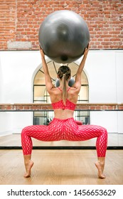 Woman in the second position plie holding a gym or pilates ball above her head viewed from the rear