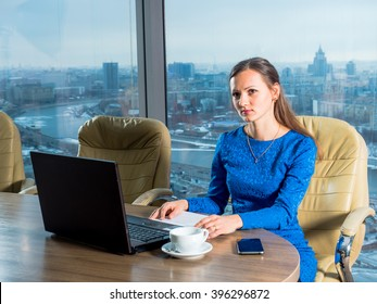 Woman secretary with dark hair sitting in the office with panoramic windows on the computer