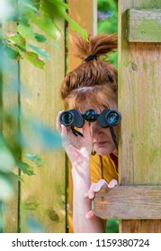 a woman is secretly watching with binoculars