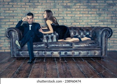 woman seduces a man on the leather couch